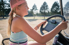 Sporty Young Girl Driving Golf...