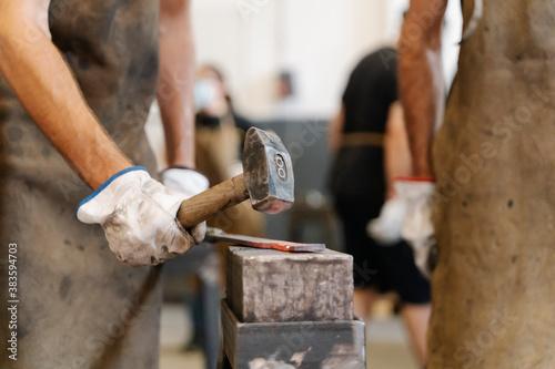 Canvas Crop blacksmiths hitting hot metal detail with hammer while forging