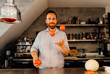 Chef Juggling Tomatoes While S...