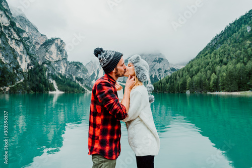 Foto Romantic kiss of a couple of adults visiting an alpine lake at Braies Italy
