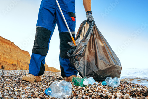 Fotografie, Obraz Close up photo of a man collecting garbage with a grabbing tool on the beach
