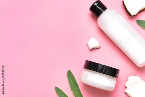 Natural organic eco cosmetics with coconut oil. Cosmetic containers with cream and lotion, broken coconut, green leaves on pink background flat lay top view. Beauty SPA branding mock-up. Blank label