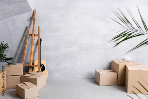 Valokuvatapetti carton boxes near easel, acoustic guitar and plants