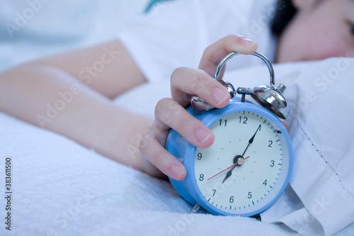 目覚まし時計を押す女性 Wallpaper Mural
