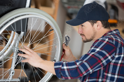 mechanic checking the spokes on a wheelchair