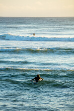 A Surfer Paddles Out Into The ...
