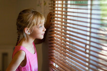 Child Looking Out Through Venetian Blinds