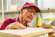 An Elderly Man Sanding A Piece...