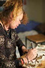Female Aboriginal Artist At Work On Possum Skin