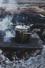 Pot Cooking On Grill On Smoking Camp Fire
