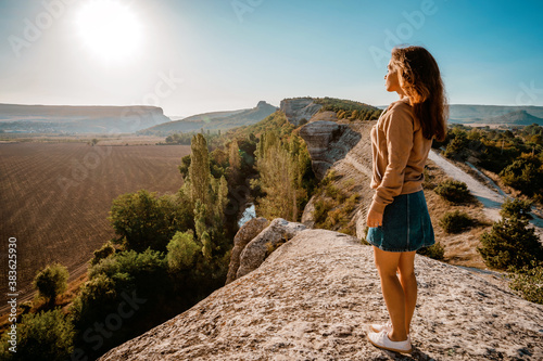 Photo Young woman standing admiring a mountaintop view looking out over distant ranges