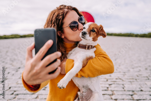 Photo A beautiful woman staying in a park with her cute little dog