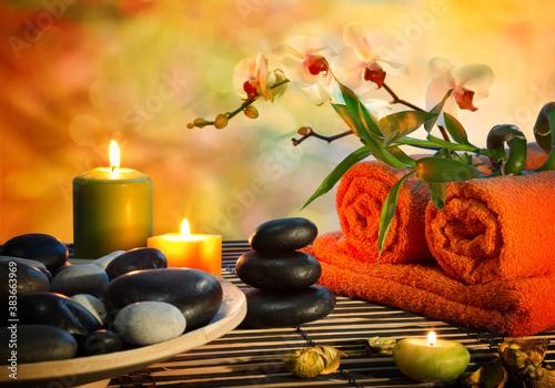 Fototapety, obrazy: Preparation for massage in orange lights and black stones