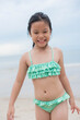 Little  girl playing on the beach on summer holidays. Children in nature with beautiful sea, sand and blue sky. Happy kids on vacations at seaside running in the water. .