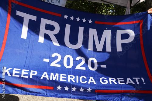 """Überzeugte Trump-Anhänger in Deutschland halten eine Fahne mit dem Wahlkampfslogan """"Trump 2020 – keep America great"""" in die Luft"""