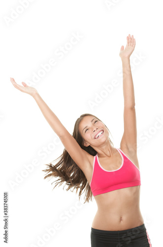 Happy fitness woman with arms raised looking up Canvas Print