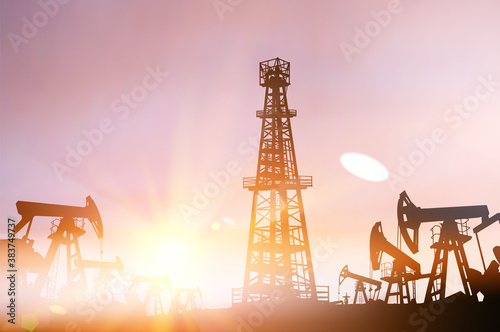 Darck silhoutte of oil rig and pumps during sunset