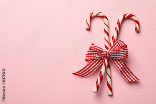 Fotografering Checkered gift bow with candy canes on pink background
