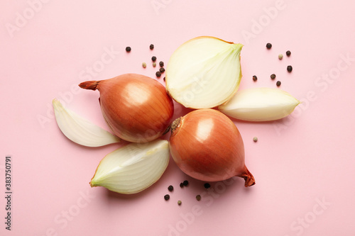 Fotografia Fresh onion and peppercorns on pink background, top view