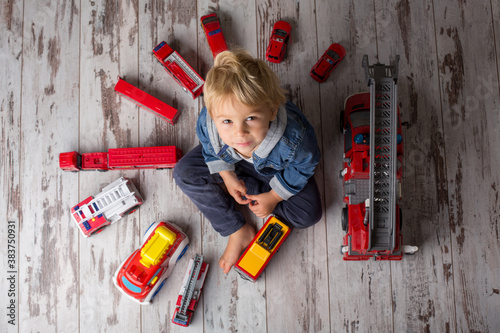 Photo Child, toddler blond boy, playing with fire trucks on the floor