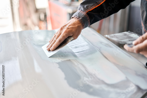 Fotomural Repairing car body, Application putty close up