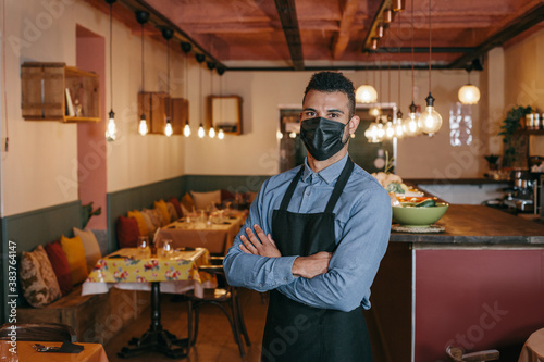 Fototapeta African American businessman wearing a protective black face mask and standing at his restaurant during Coronavirus. Proud owner with his arms crossed and looking at the camera with a defiant gaze. obraz