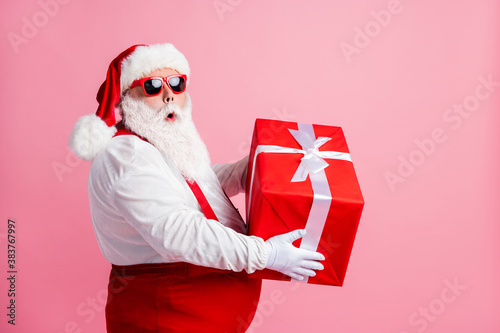 Profile side photo astonished fat santa claus hold big gift box he get x-mas christmas night spirit jolly event wear headwear suspenders overall sunglass isolated pastel color background