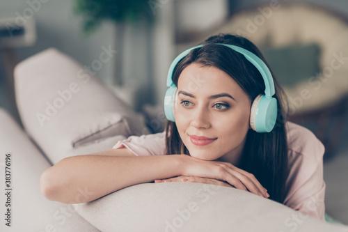 Fototapeta Photo portrait of young girl listening to music wearing cyan headphones sitting