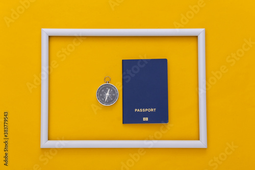 Fotomural Compass and passport in white frame on yellow background