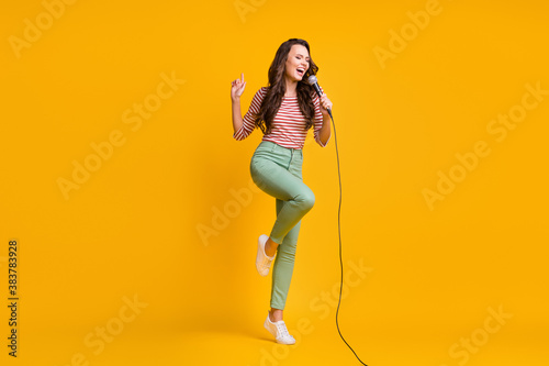 Full length body size photo of girl singing song with microphone in karaoke isolated on bright yellow color background