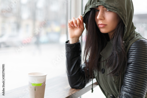 girl in hood is drinking coffee in street cafe