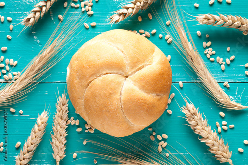 Kaiser roll and wheat ears on turquoise table