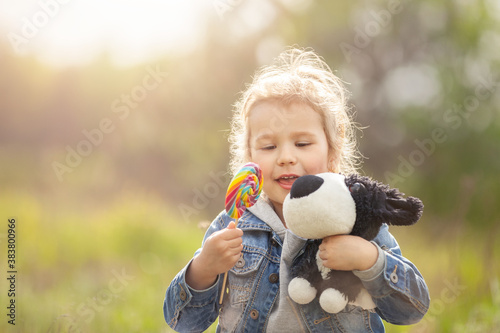 Smiling little girl with lollipop playing toy on meadow Wallpaper Mural