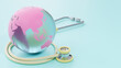 Leinwandbild Motiv Pink globe looks crystal clear with stethoscope yellow pastel color on blue background. 3D Render.