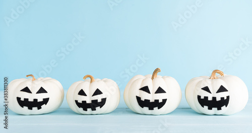 White ghost pumpkin on pastel blue background. Halloween decoration concept.