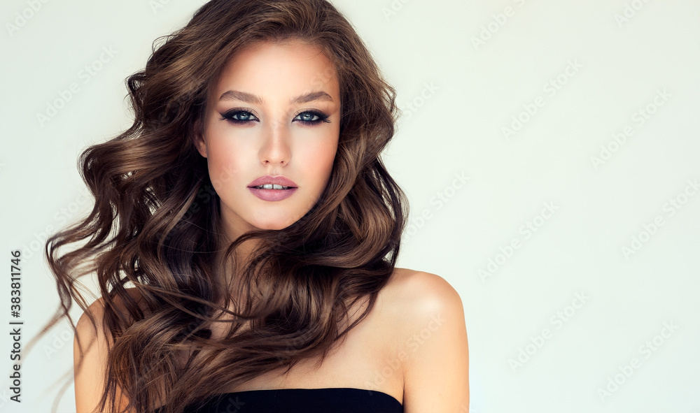 Fototapeta Beautiful model girl with long wavy and shiny hair . Brunette woman with curly hairstyle