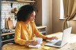 An african-american young woman is using laptop computer for remote work or studying online, she takes notes watching webinars or classes at kitchen table at home