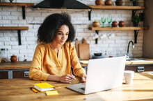 Entrepreneur Young Woman Talking Using Laptop In Home Office. An African-american Woman Concentrated Looks At Computer Screen