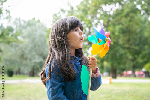 Valokuvatapetti Adorable black haired girl playing in park, holding pinwheel and blowing on toy