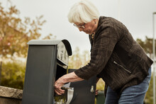 Senior Woman Standing Near Mailbox
