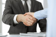 Unknown business man and woman are shaking hands finishing contract signing, close-up. Business and handshake concept
