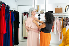 Shop Assistant Adjusting Dress On Female Customer. Woman Trying On Clothes In Fashion Store. Buying Clothes In Boutique Concept