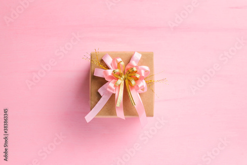 Foto Paper gift box with pink ribbon on pink background, present for giving in specia