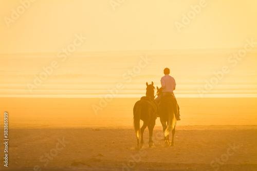 Valokuva Horse riding on the beach at sunset.