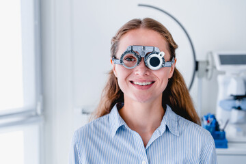 Smiling young female patient checking up sight using ophthalmic glasses
