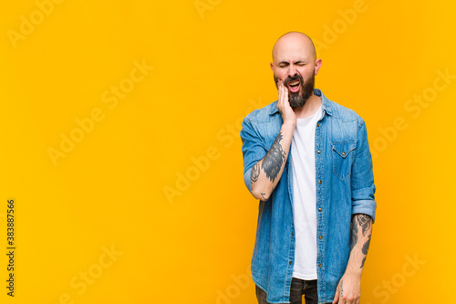 Fotografía young bald and bearded man holding cheek and suffering painful toothache, feelin