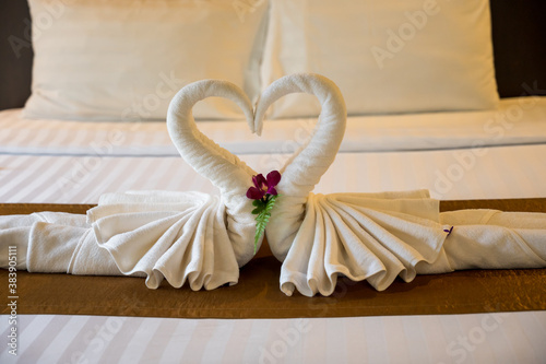 The white towel folded into swan shape and placed like heart shape on bed, luxur Fototapet