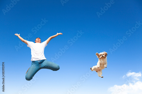Fototapeta young man and dog jumping in the sky
