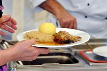 Eine Hand, Die Einen Teller Mit Handl, Knödel Und Sauerkraut Hält Vor Einem Koch An Der Essenausgabe.