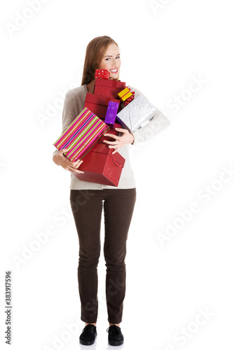 Beautiful casual woman holding presents in boxes.